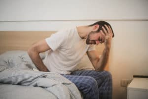 young-man-in-sleepwear-suffering-from-headache-in-morning-3771115